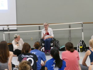 Tanya is sitting in her wheelchair on the right side of the photo with the rest of the Body Shift Collective dancers and teachers at the Texas Dance Improvisational Festival. Tanya in front of students telling the story of how she ended up in the dance world. Silva is sitting on the floor laughing.