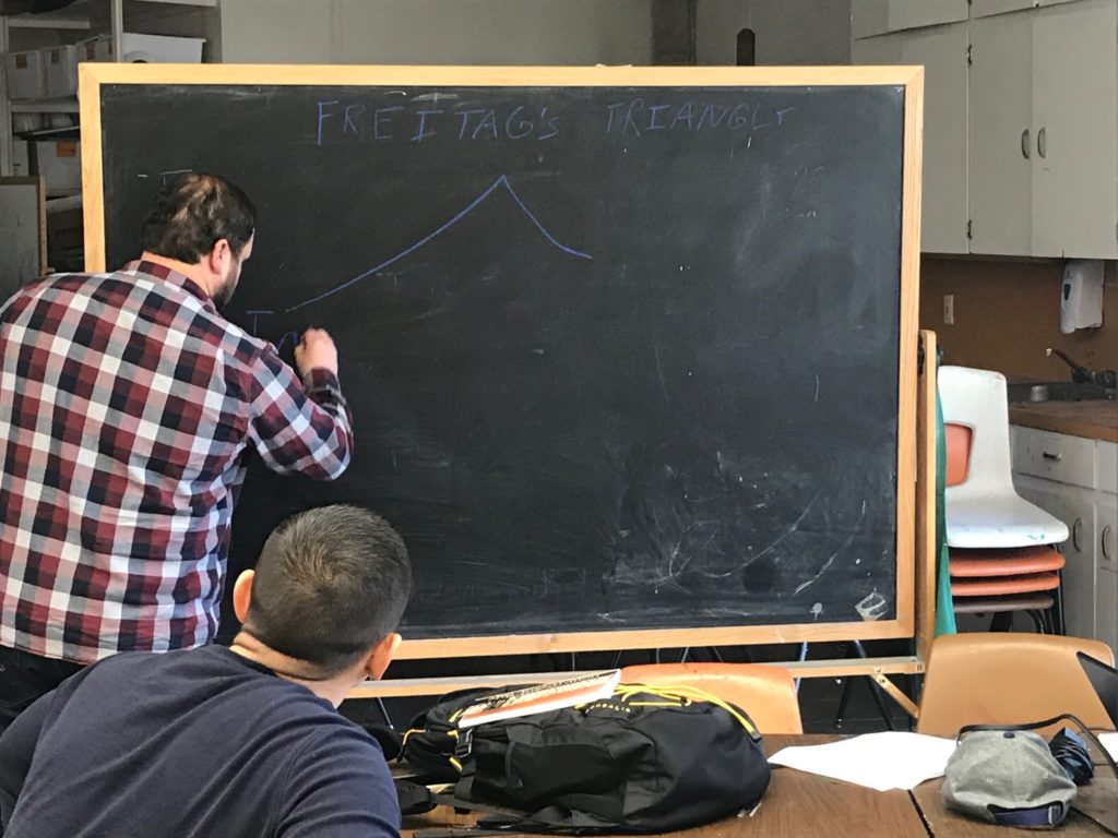 Instructor Clayton Bradshaw writing on a blackboard with a student seated at a table