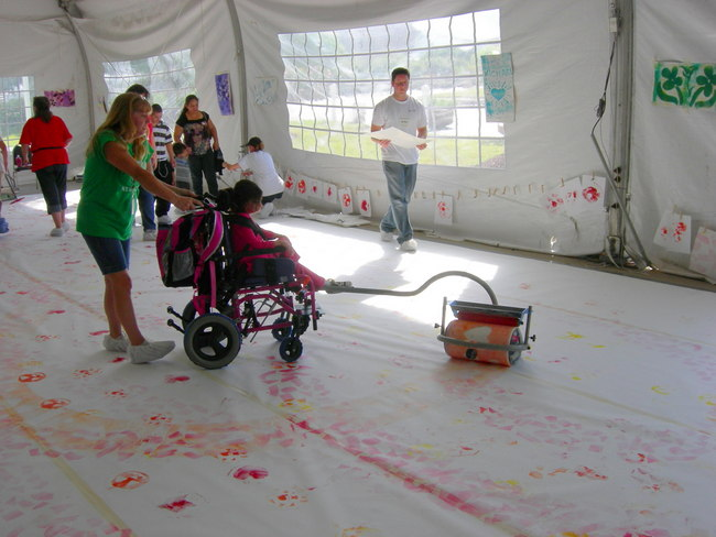 girl in wheelchair using paint roller on floor
