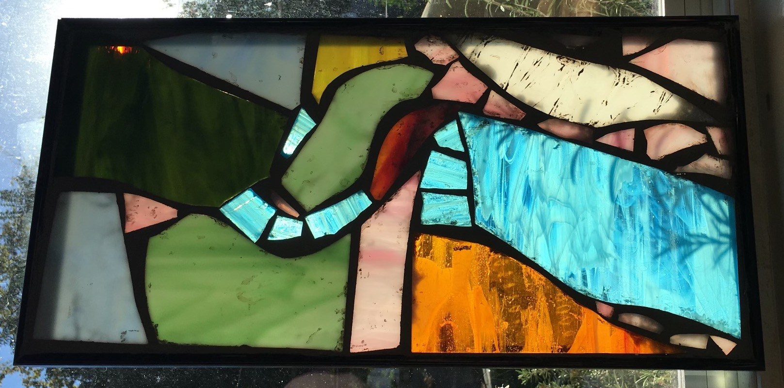 A framed abstract stained glass piece in a window