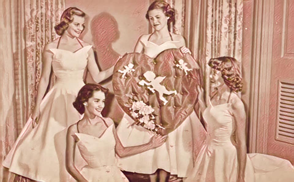 Four women in 50s style cocktail dresses holding a large valentine heart with a cupid in the middle